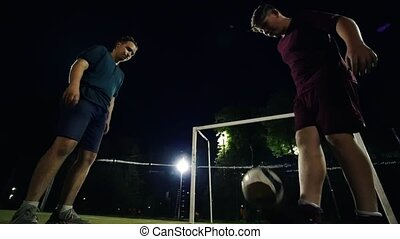 Two young men alternately kick the ball on the field at night
