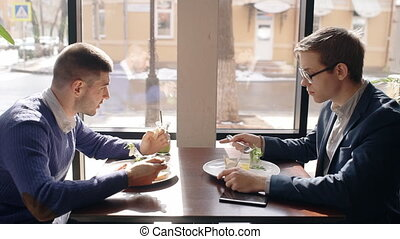 Two young men are eating and talking, sitting at table in cafe.