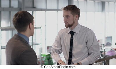 Two young men are talking, standing in auto salon, business...