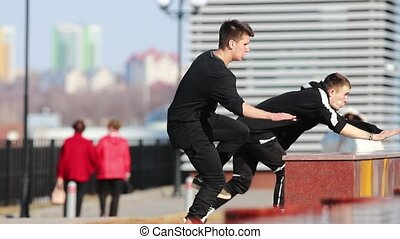 Two young men doing acrobatic parkour tricks. Mid shot