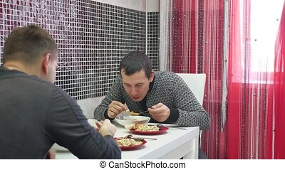 Two Young Men Eating Breakfast In Kitchen Together -...