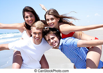 Two young men giving piggy back to his women and standing...