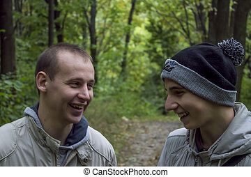 two young men laughing in the forest