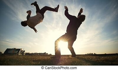 Two young men outdoors fighting on the sunset, slow motion