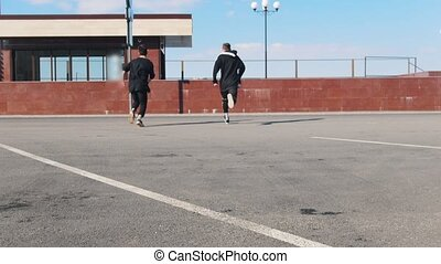 Two young men overcoming obstacles on the urban streets. Mid...