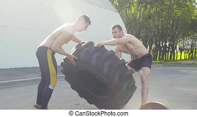 Two young men rolling a wheel in order to do crossfit...