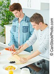 two young men rolling out dough