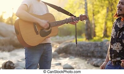 Two young men singing, playing guitar and spending weekend outdoors in the sunset. Slow motion.
