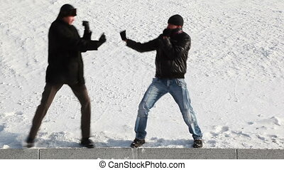 men snowy winter playfully imitating boxing match - two...