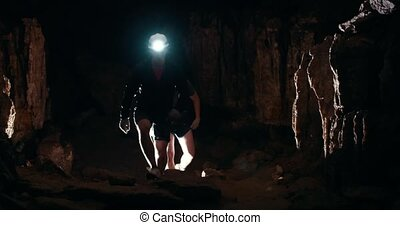 Two young men speleologists with flashlight walks in a dark...