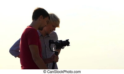 Two Young Men Stand And Look at a Stedicam With New Video...