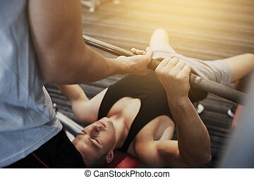 two young men with barbell flexing muscles in gym - sport, ...