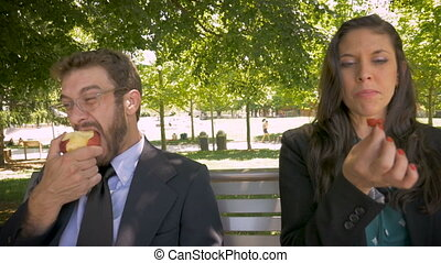 Two young millennial office executives eating healthy fruit outside close up