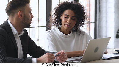 Two young mixed race business partners discussing project ideas at brainstorming meeting in office, head shot. Smart african ethnicity employee sharing working information with confident male leader.