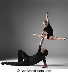two young modern ballet dancers on gray studio background -...
