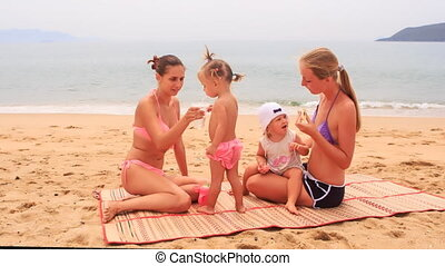 two young mothers and little daughters sit on mat bite