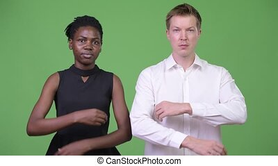 Two young multi-ethnic business couple with arms crossed together