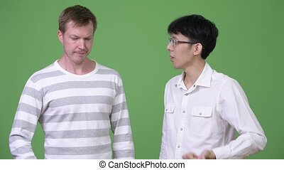 Two young multi-ethnic businessmen confused with different...