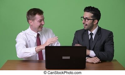 Two young multi-ethnic businessmen working together against green background