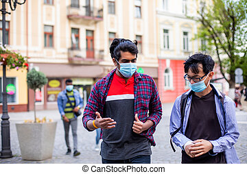 Two young multiracial friends in masks chatting outdoors