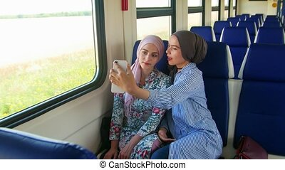 Two young muslim woman in hijab, taking selfie with phone. -...