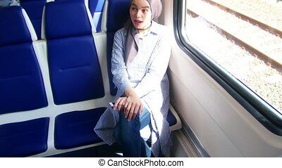 Two young muslim woman traveling by train