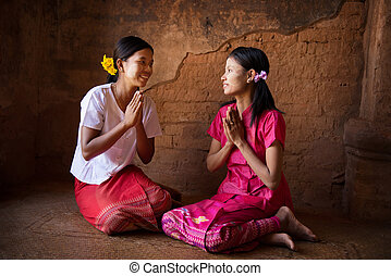 Two young Myanmar girls praying in temple