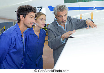 Two young people being shown wing of aircraft