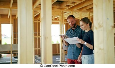 Two Young People Discussing Construction of a House