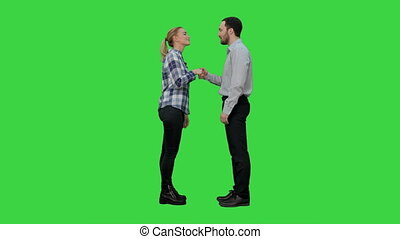 Two young people in casual shake hands, look at camera and thumb up on a Green Screen, Chroma Key.
