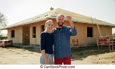 Two Young People in Front of Their New House