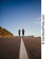 Two young people jogging on country road