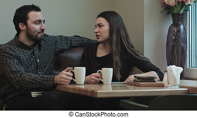 Two young people looking communicate in cafe