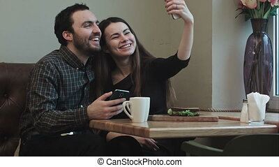 Two young people makeing selfy while in cafe