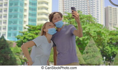 Two young people man and woman communicate wearing medical face masks in the wrong way. Their masks do not cover their noses. Wrong-way of using a face mask