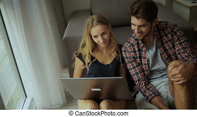 Two young people relaxing with laptop at home.