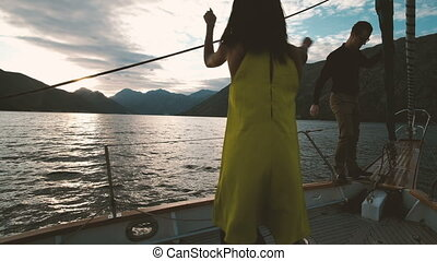 Two young people sailing on sailboat and dancing on deck outdoors.