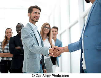 two young people shake hands