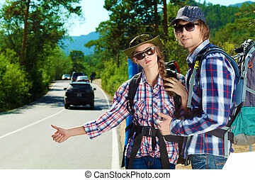 hitchhiking - Two young people tourists hitchhiking along a ...