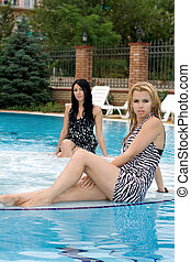 Two young playful girlfriends in pool