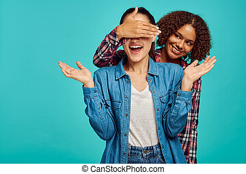 Two young playful ladies, blue background, positive emotion. Face expression, female person looking on camera in studio, emotional concept, feelings