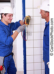 Two young plumbers larking about with a voltmeter