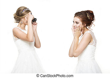 Two young pretty brides making wedding photo in studio