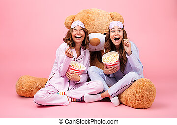 Two young pretty girls dressed in pajamas laughing