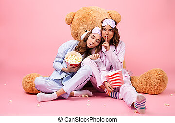 Two young pretty girls dressed in pajamas showing silence...