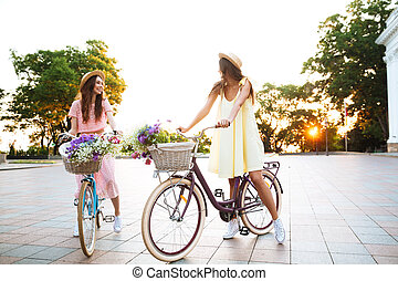 Two young pretty women in dresses sitting on retro bicycles