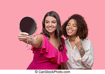 Two young pretty women looking at themselves in the mirror.