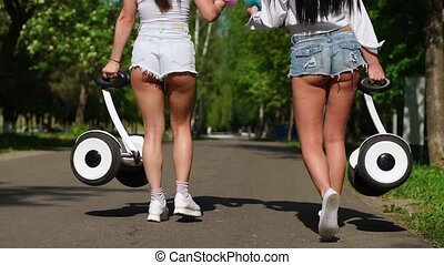 Two young sexy brunettes with loose hair in short denim...