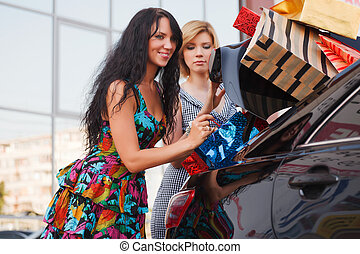 Two young shoppers on a car parking