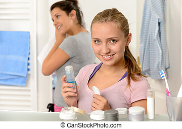 Two young sisters getting ready in bathroom